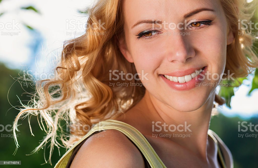 Blond woman, flipping curly hair. Sunny summer nature. stock photo