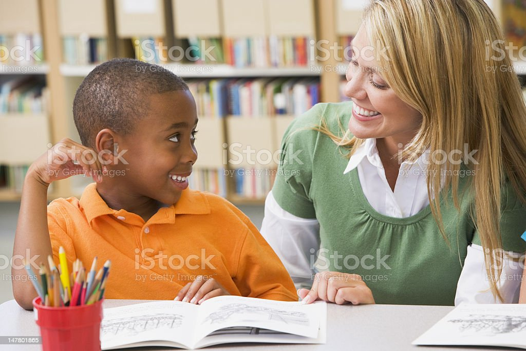Blond woman helping young boy with school work stock photo