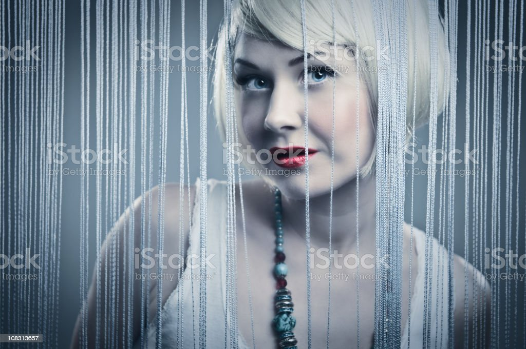 Blond woman hiding behind curtain royalty-free stock photo
