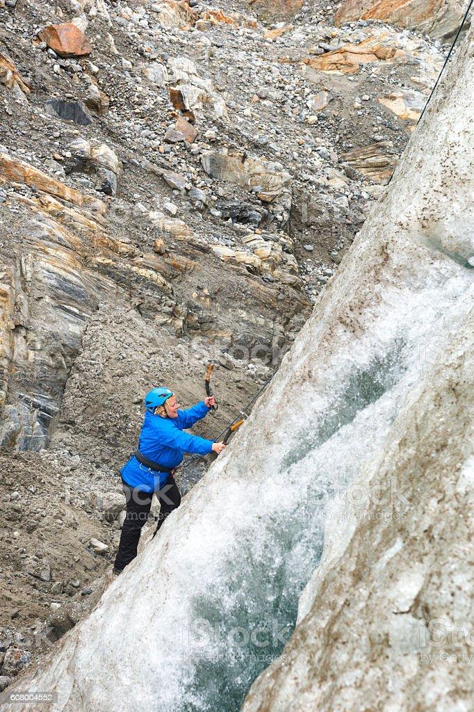 Blond woman ice climbs in Alaska stock photo