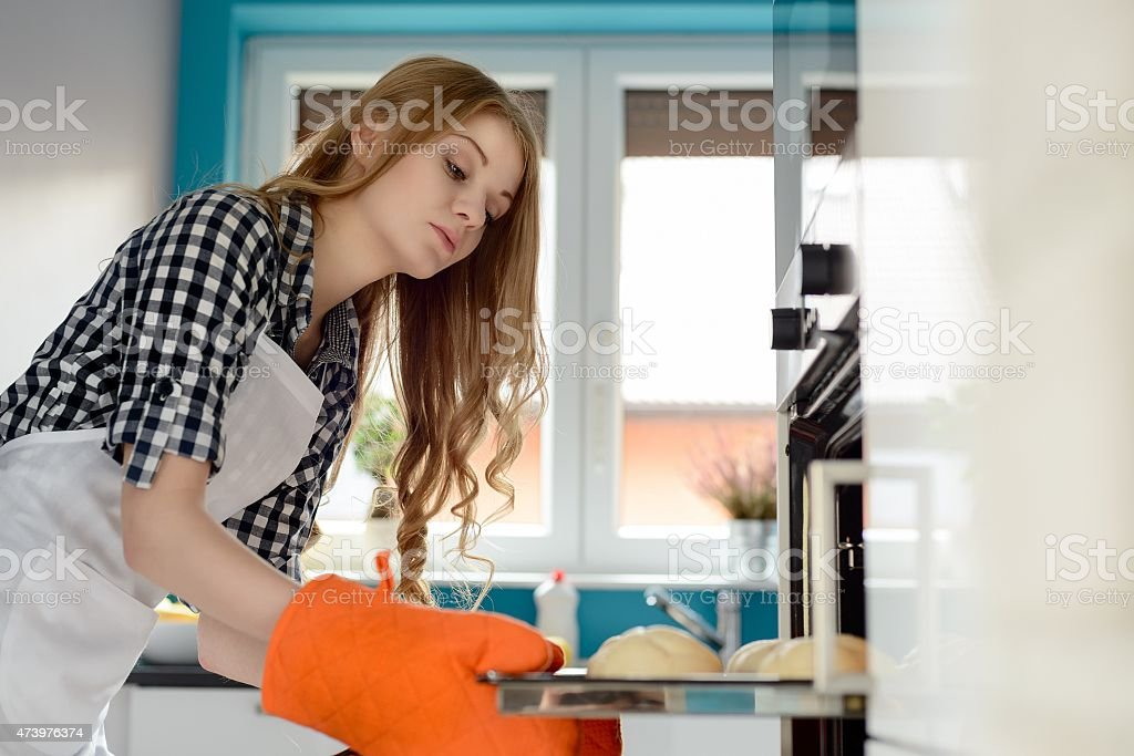 blond woman in a white apron bakes bread rolls stock photo