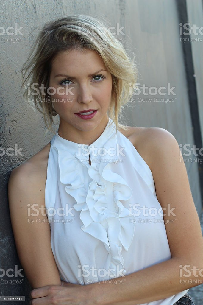 Blond woman in classy white silk blouse stock photo