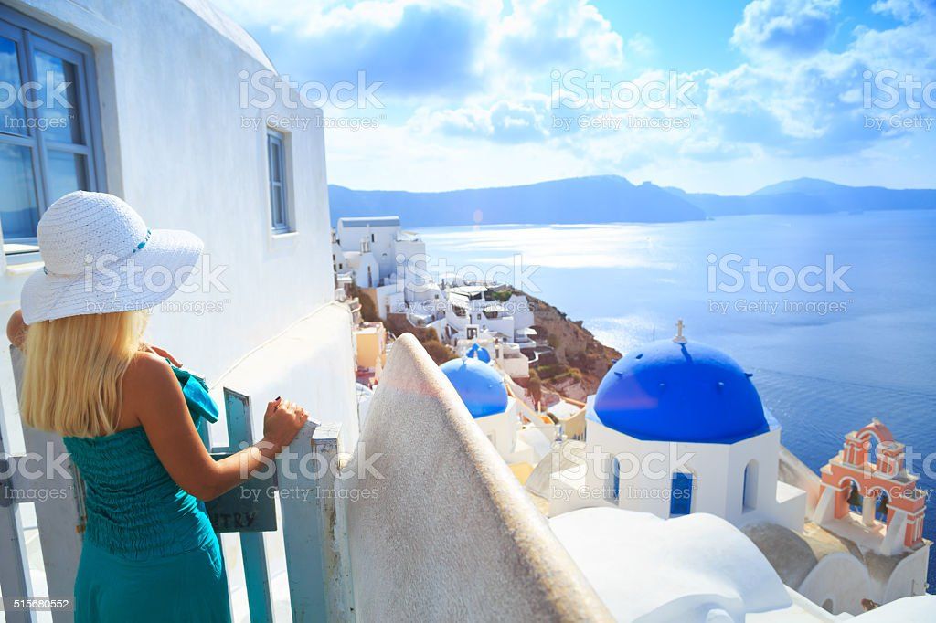 Blond woman in front of town Oia at Santorini stock photo