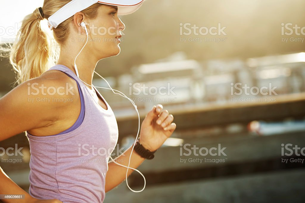 Blond woman jogging while wearing ear buds stock photo