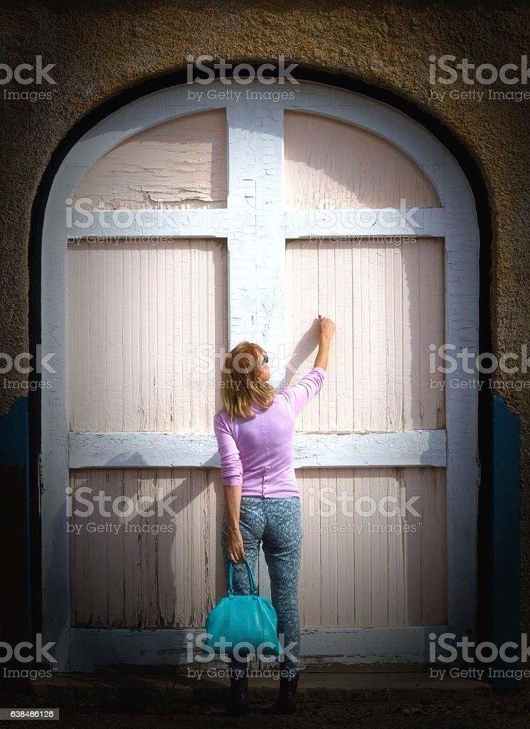 Blond Woman Knocks on Old Barn Door stock photo