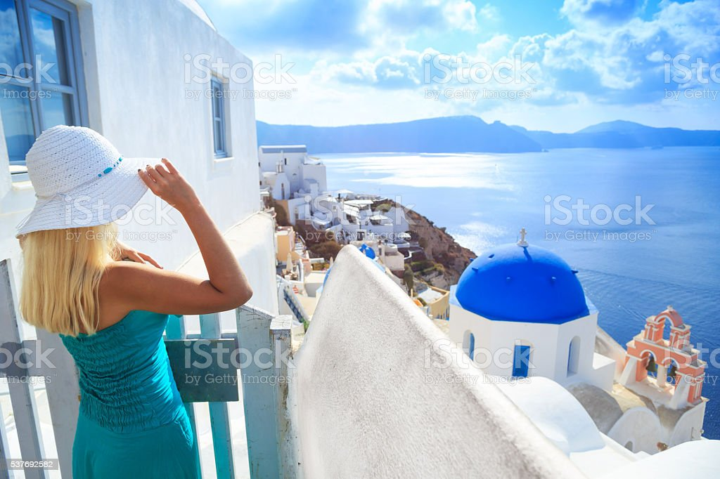 Blond woman looking at view of Santorini, Greece stock photo