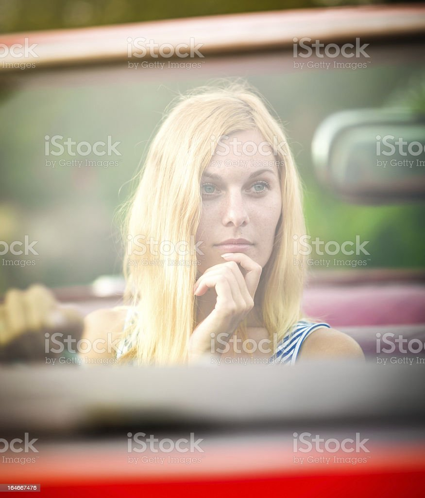 Blond woman looking into rear view mirror royalty-free stock photo