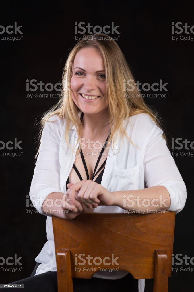 Blond woman on a dark background stock photo