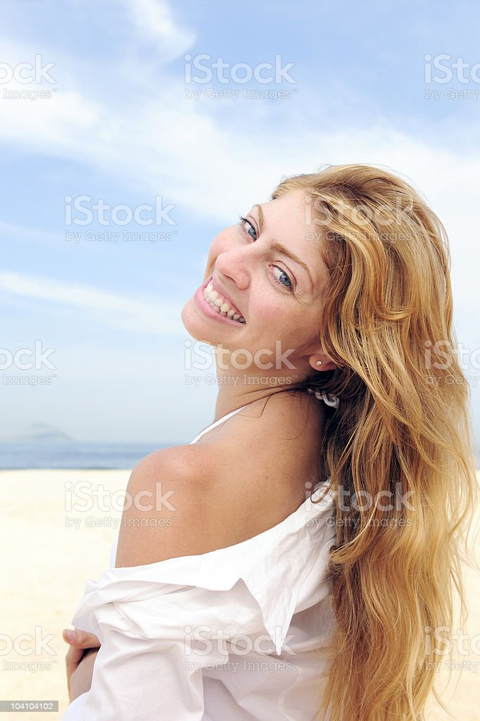 Blond woman on the beach laughing stock photo