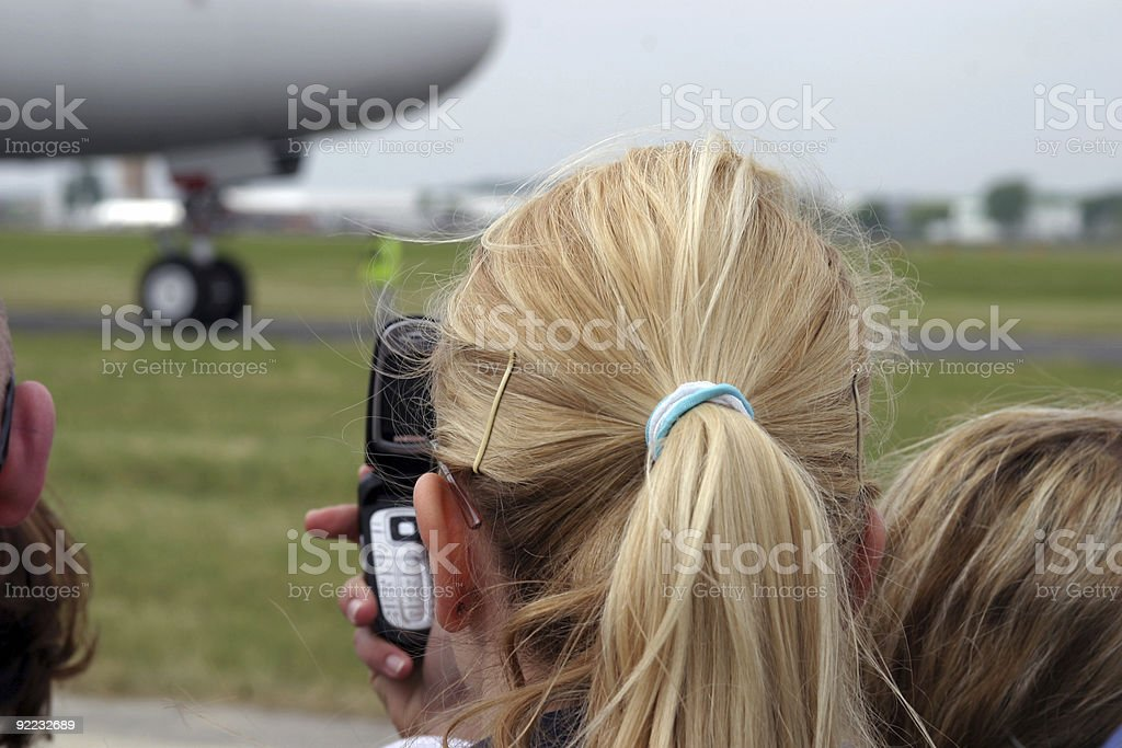 Blond woman photographing departing airplane royalty-free stock photo