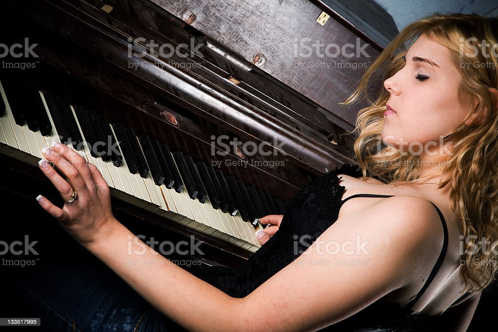 Blond woman playing the piano stock photo