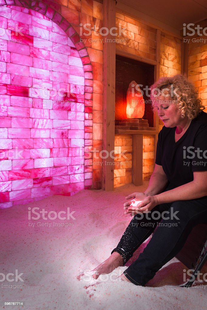 Blond woman plays with sand in salt cave stock photo