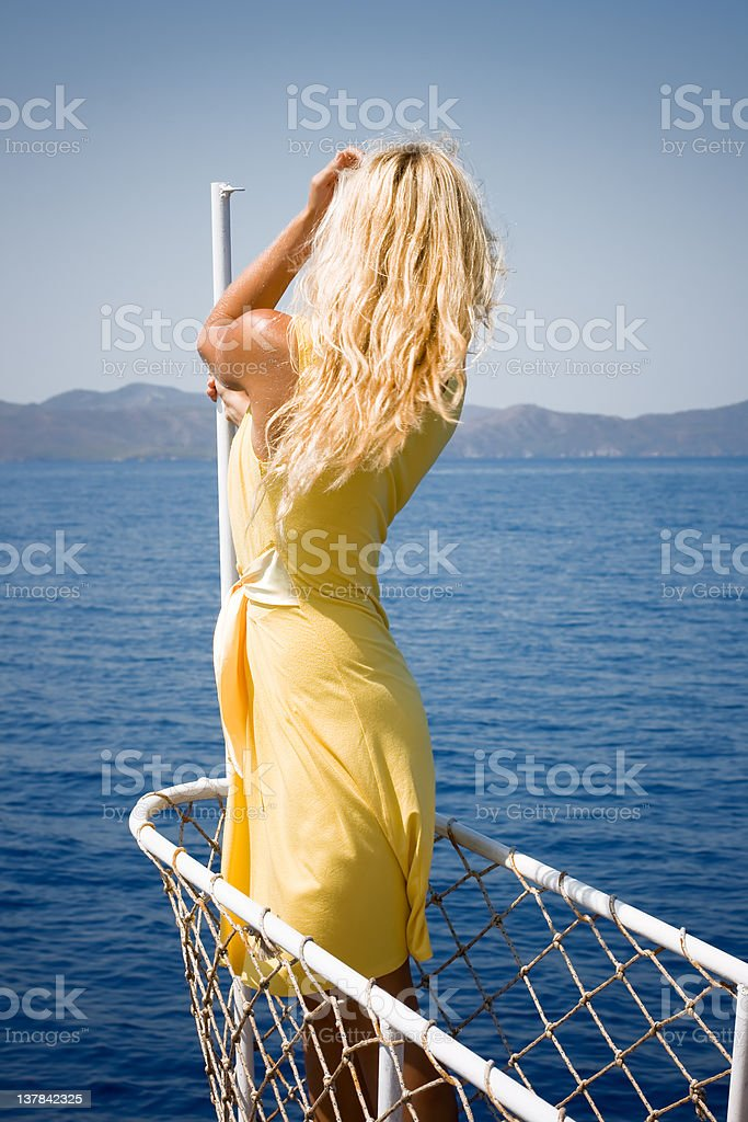 Blond woman posing on the ship's bow royalty-free stock photo