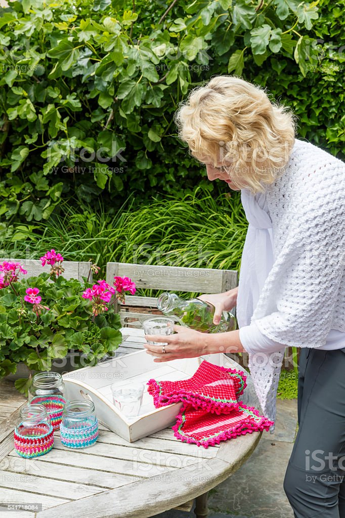Blond Woman Pouring Water In The Garden stock photo