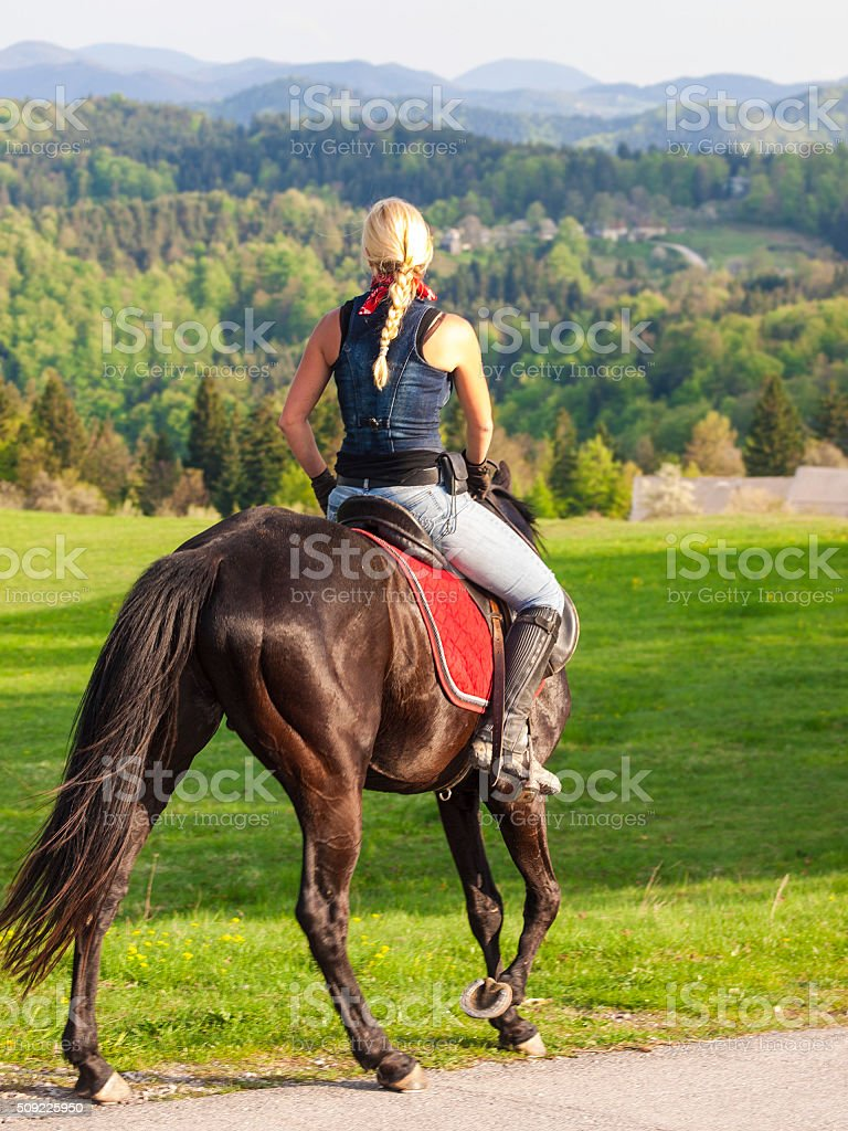 Blond woman riding black horse stock photo