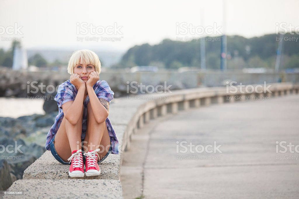Blond woman sitting on parapet head in hands stock photo