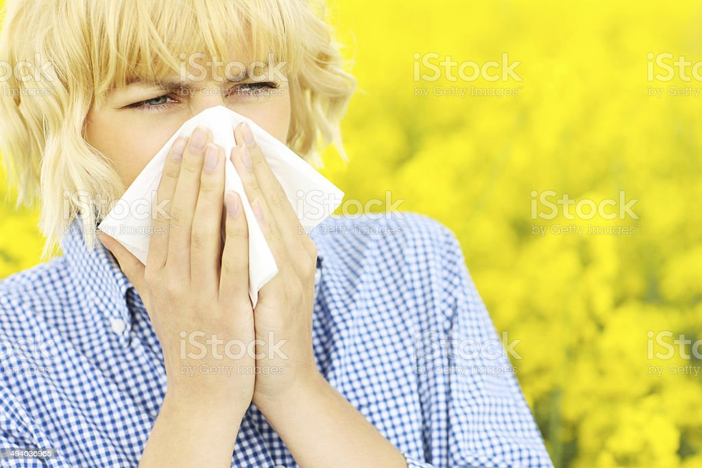 Blond woman sneezing in field of flowers stock photo
