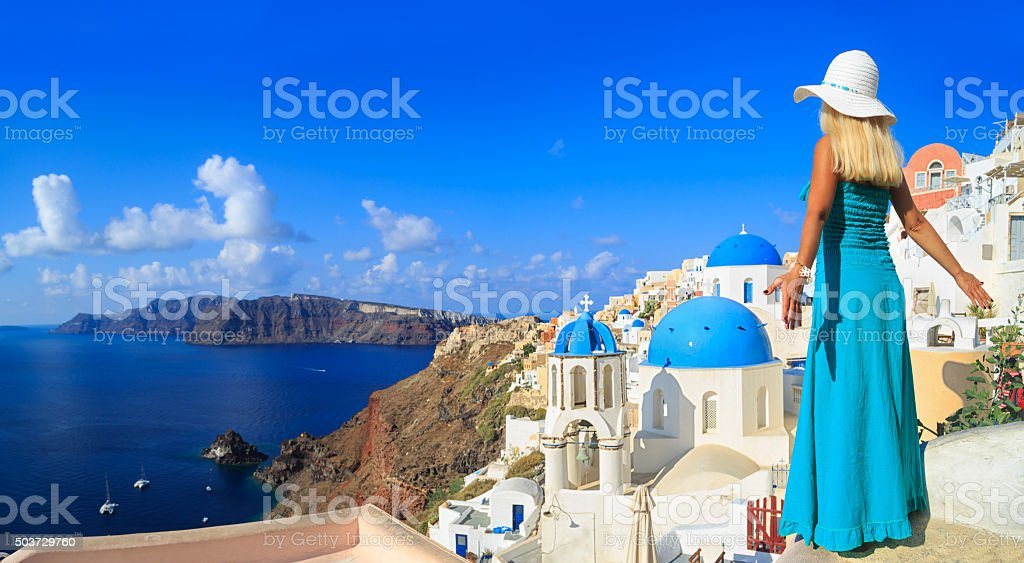 Blond woman standing on roof in Santorini-rear view stock photo