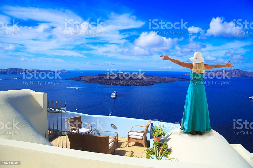 Blond woman standing on rooftop in Santorini stock photo