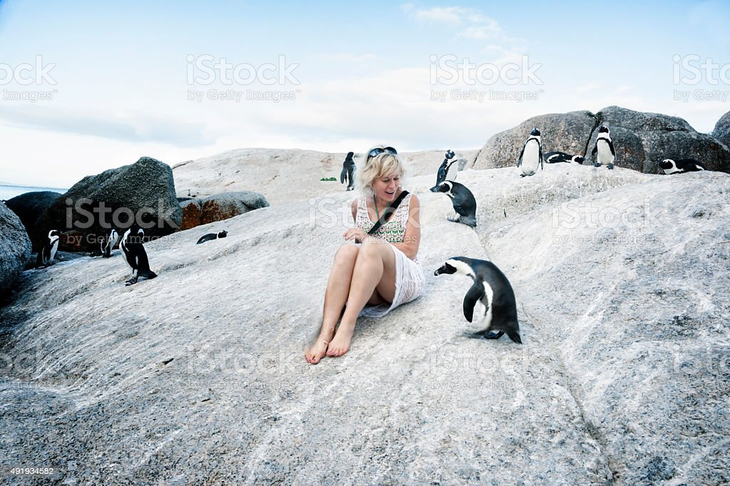 Blond woman surrounded by approaching penguins stock photo