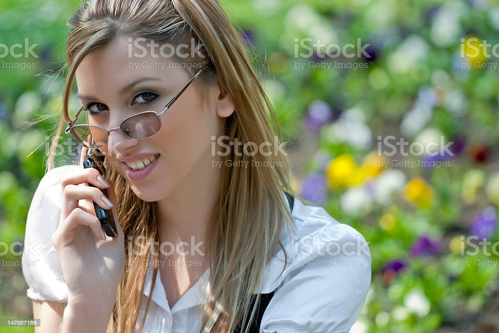 Blond woman talking on mobile phone in the park royalty-free stock photo