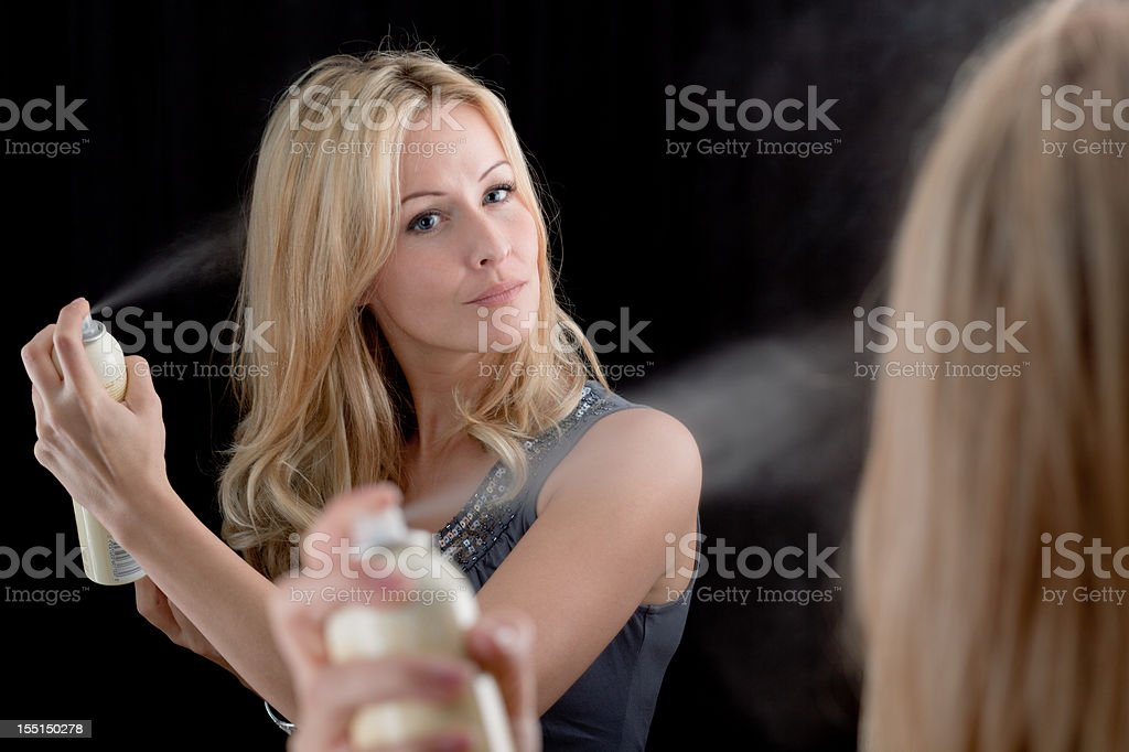 Blond woman using hairspray in front of mirror stock photo