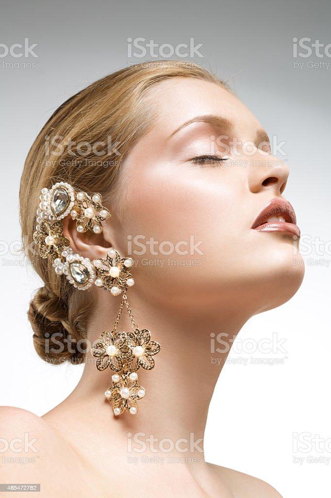 blond woman wearing big golden earrings stock photo