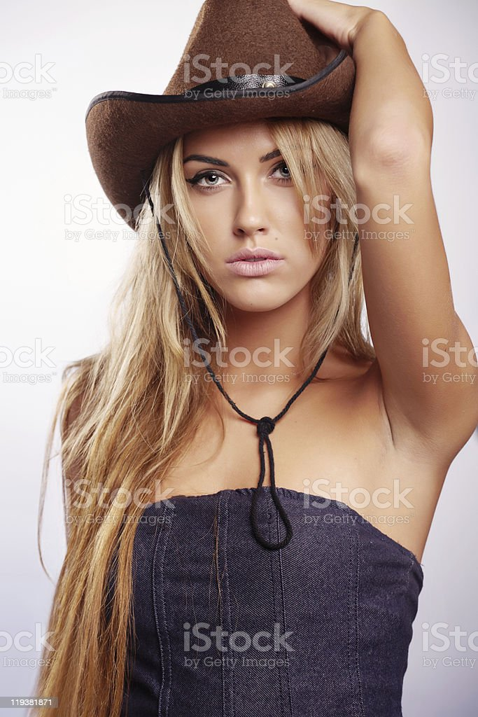 Blond woman wearing cowgirl hat stock photo