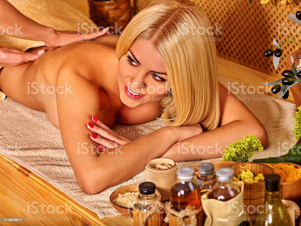 Blond woman with beautiful long hair getting massage in tropical stock photo
