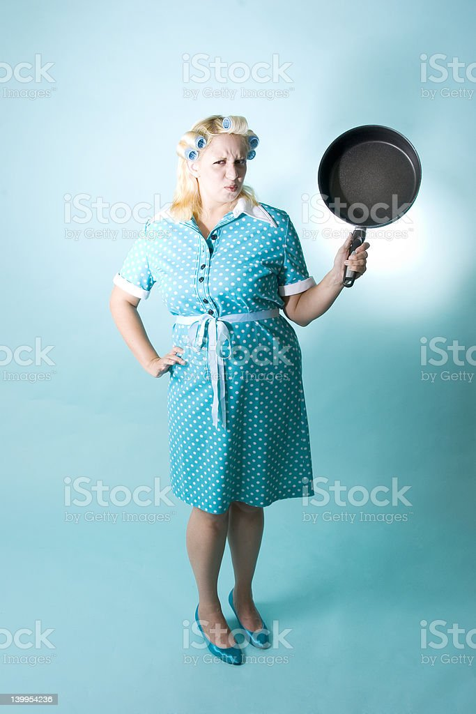 Blond woman with curlers in her hair and frying pan royalty-free stock photo