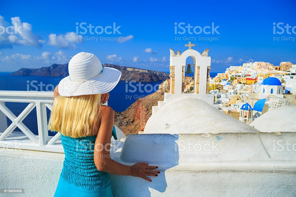 Blond woman with hat looking at Santorini stock photo