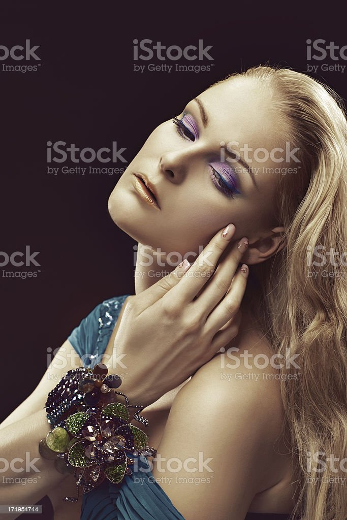 blond woman with multicolored make-up looking down royalty-free stock photo