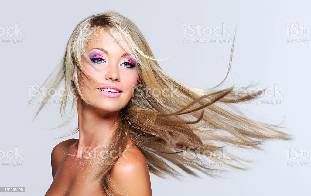 Blond woman with pink makeup throwing her hair royalty-free stock photo