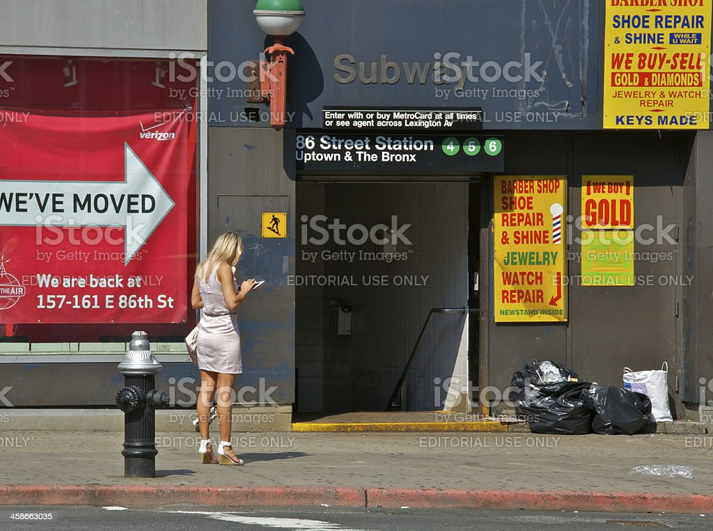 Blond woman with tablet computer near subway entrance, NYC stock photo