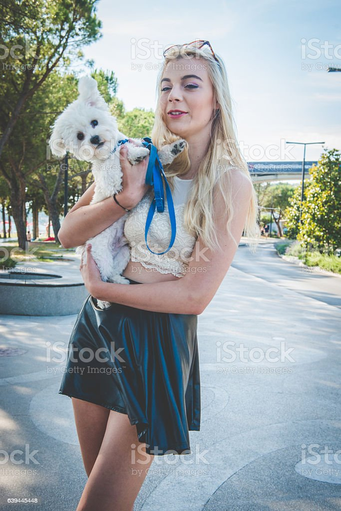 Blond Woman with White Small Dog in Portorose, Slovenia, Europe stock photo