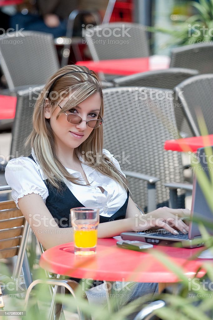 Blond young business woman with laptop in a cafe royalty-free stock photo