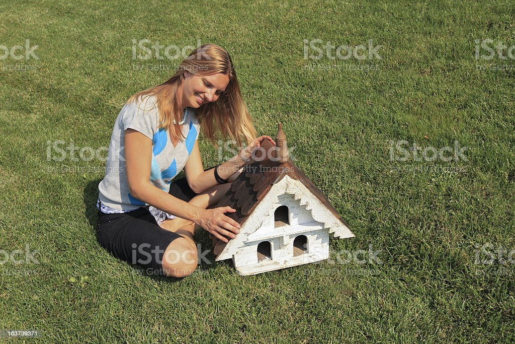 Blond young girl checking her wooden little birds house (nestle) royalty-free stock photo
