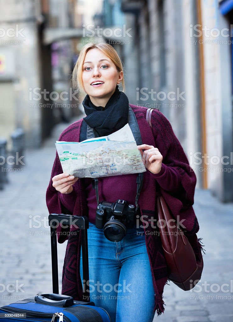 Blond young girl holding map and looking for her way stock photo