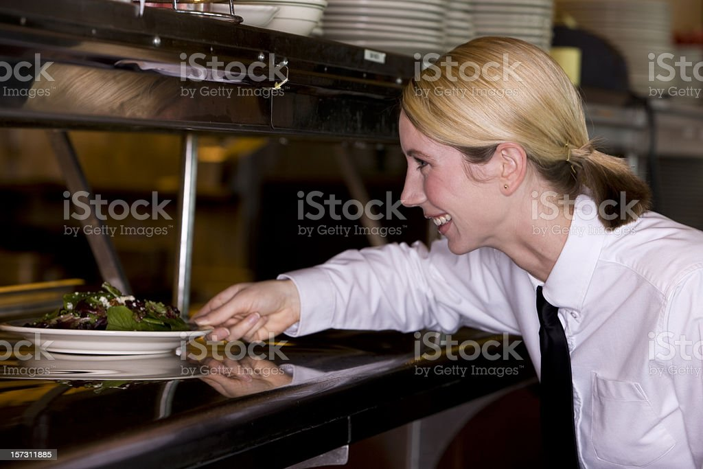Blond Young Woman as Restaurant Server in Kitchen, Copy Space royalty-free stock photo