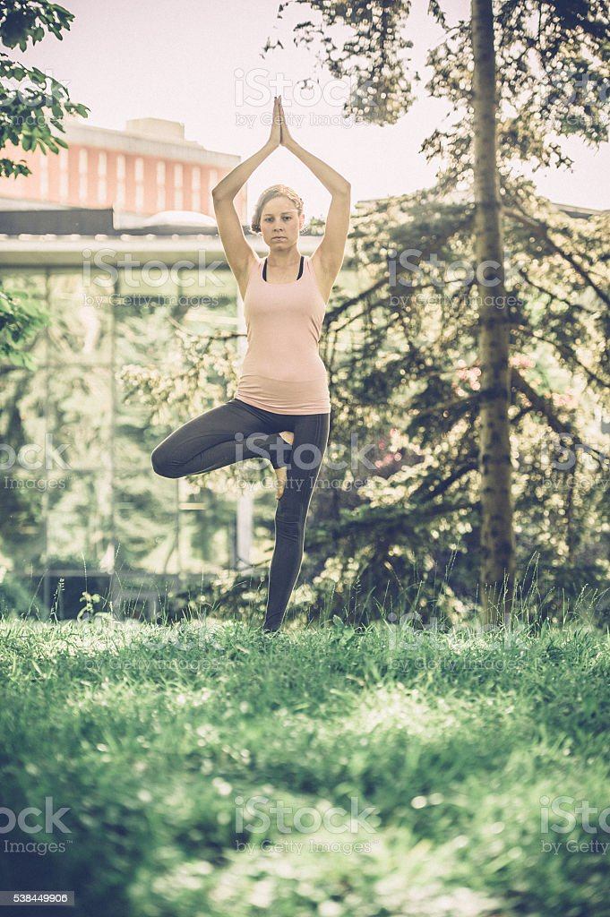 Blond young woman doing tree yoga pose stock photo