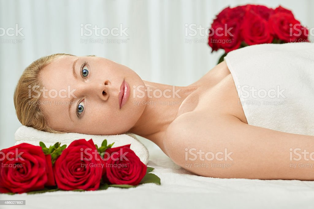 Blond Young Woman on Massage Table with Red Roses royalty-free stock photo