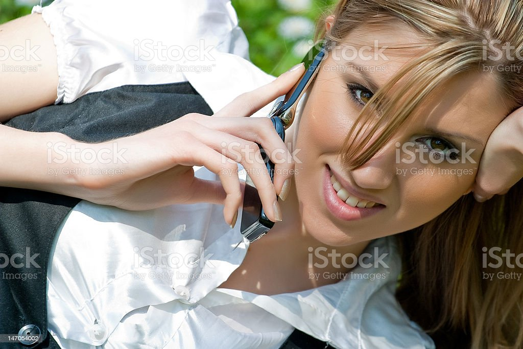 Blond young woman talking on mobile phone in the park royalty-free stock photo
