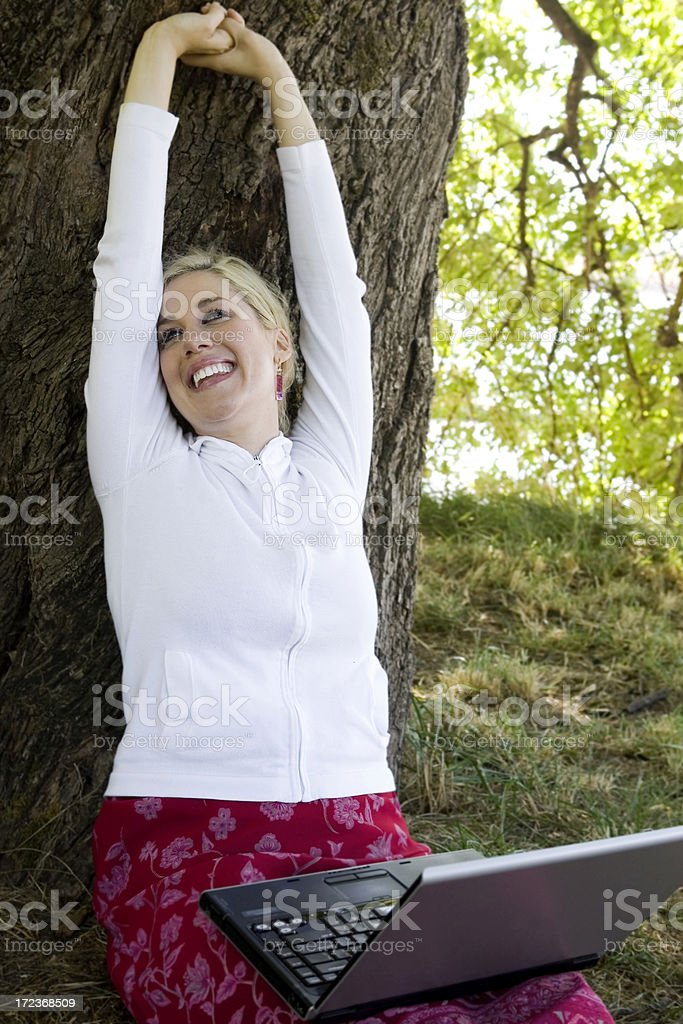 Blond Young Woman Using Laptop, Stretching Outside Beaneath Tree Canopy royalty-free stock photo
