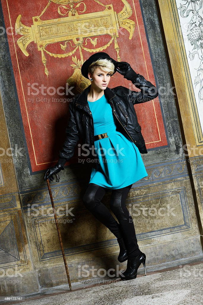 Blond young Woman with Cool Fashion Outfits before Old Wall stock photo