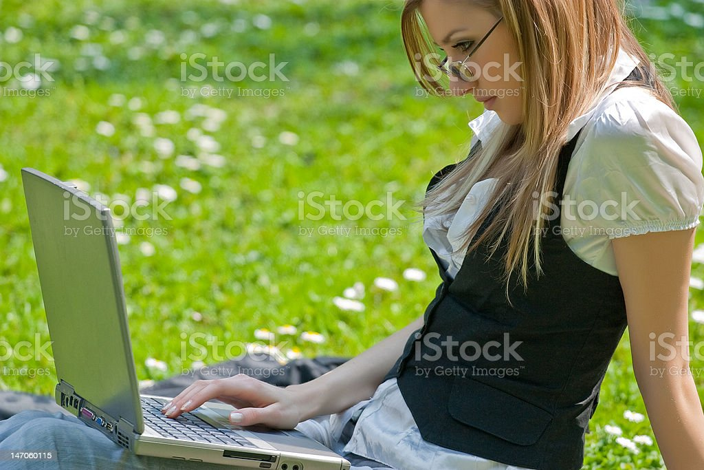 Blond young woman with laptop in the park royalty-free stock photo