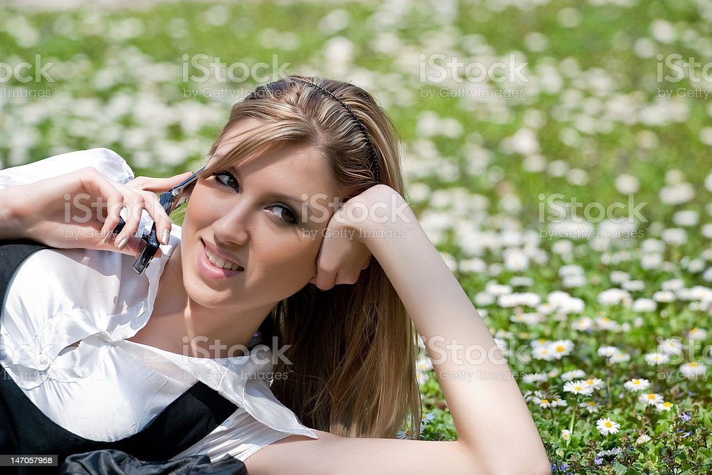 Blond young woman with mobile phone in the park royalty-free stock photo