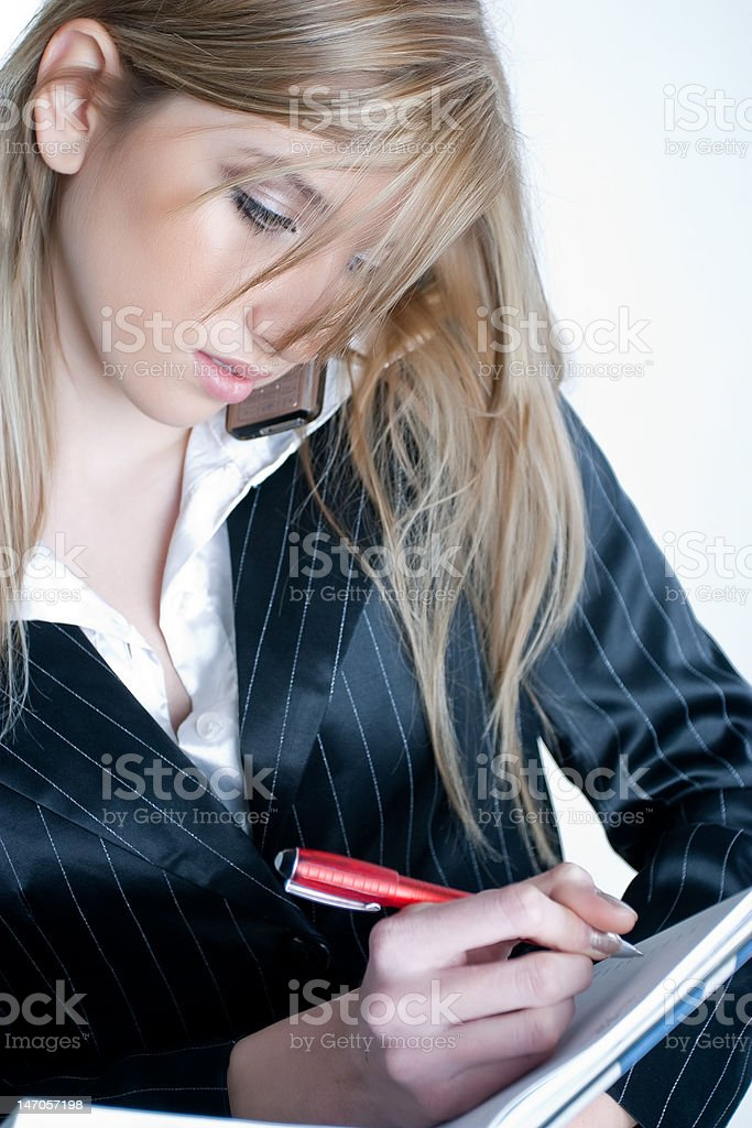 Blond young woman with notebook and a pen writing royalty-free stock photo