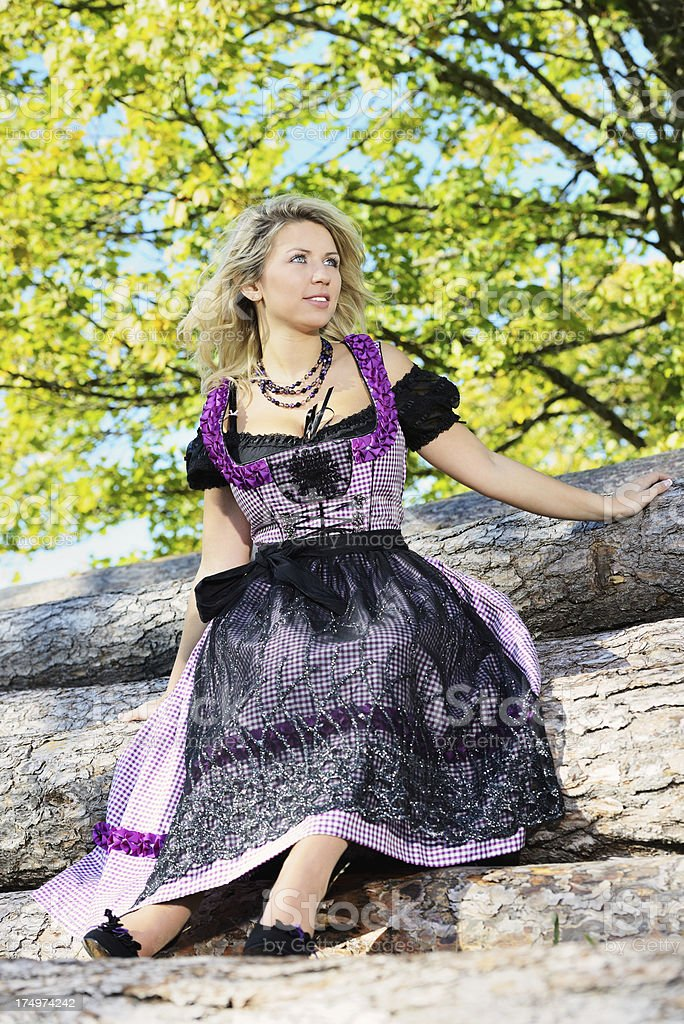 Blond Young Woman with Purple Dirndl Dress stock photo