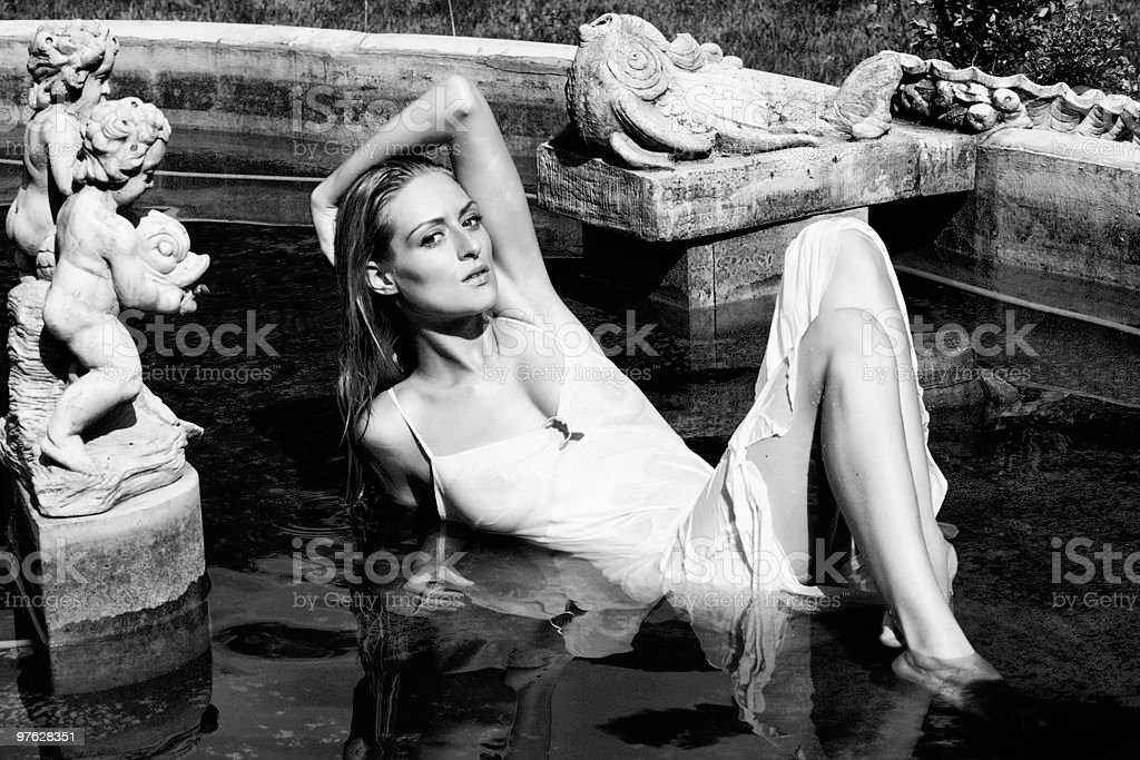Blond young woman with white dress, lying in a fountain stock photo
