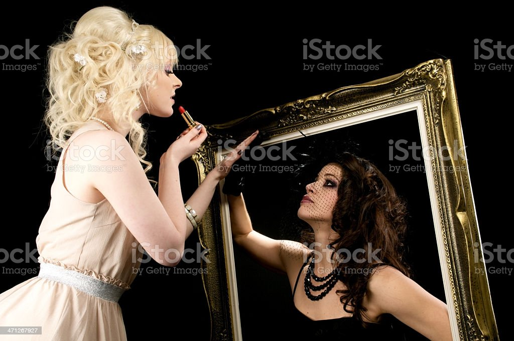 Blonde applies lipstick with dark reflection. royalty-free stock photo
